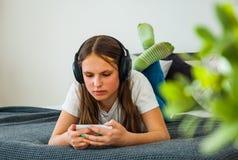 La muchacha del adolescente se divierte con la colocación móvil en la cama que escucha la música de un smartphone Fotografía de archivo