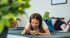 La muchacha del adolescente se divierte con la colocación móvil en la cama que escucha la música de un smartphone Imágenes de archivo libres de regalías