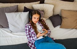 La muchacha del adolescente se divierte con la colocación móvil en la cama que escucha la música de un smartphone Foto de archivo