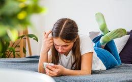 La muchacha del adolescente se divierte con el smartphone que pone en la cama Imagen de archivo libre de regalías