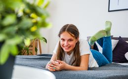 La muchacha del adolescente se divierte con el smartphone que pone en la cama Fotos de archivo