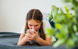 La muchacha del adolescente se divierte con el smartphone que pone en la cama Imagenes de archivo