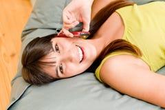 La muchacha del adolescente se relaja a casa - en el teléfono Imágenes de archivo libres de regalías
