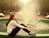 La muchacha del adolescente se sienta al lado de la fuente en parque de la primavera Imagen de archivo