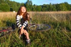 La muchacha del adolescente se sienta con la bicicleta en el campo del país Imagen de archivo libre de regalías