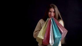 La muchacha del aspecto caucásico en un suéter hecho punto, presionó cerca de él y sostiene reservado una pila de bolsos del rega metrajes