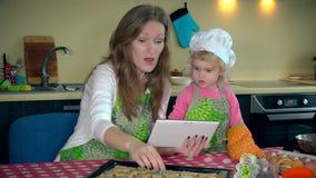 La muchacha del ayudante ayuda a su madre con las galletas de la hornada Mujer con el ordenador de la tablilla metrajes