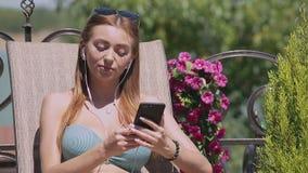 La muchacha del bikini se relaja en silla de cubierta con música metrajes