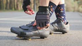 La muchacha del ciclista aprieta los zapatos del camino antes del paseo de la bicicleta Cierre para arriba almacen de metraje de vídeo