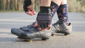 La muchacha del ciclista aprieta los zapatos del camino antes del paseo de la bicicleta Cierre para arriba C?mara lenta almacen de video