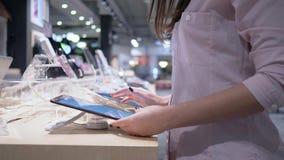 La muchacha del cliente en tienda de la electrónica utiliza la tableta moderna cerca de escaparate de la presentación almacen de metraje de vídeo