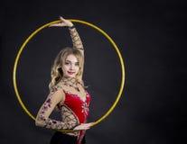 La muchacha del contorsionista en traje de la etapa con los aros fotos de archivo libres de regalías