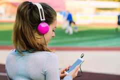 La muchacha del deporte en auriculares rosados selecciona música Imagen de archivo libre de regalías