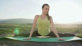 La muchacha del deporte en el top de la montaña realiza estirar y la relajación de los músculos después de un entrenamiento duro  almacen de video