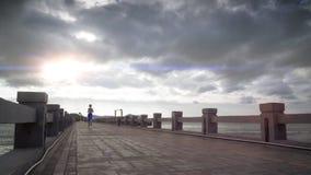 La muchacha del deporte está corriendo en la playa almacen de video