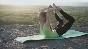 La muchacha del deporte realiza ejercicios de la yoga en el al aire libre Los soportes rubios delgados de la muchacha de la opini almacen de metraje de vídeo