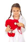 La muchacha del doctor examina el juguete del corazón Imagen de archivo libre de regalías
