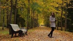La muchacha del encanto bebe el café de una taza mientras que se sienta en un banco en parque del otoño almacen de video