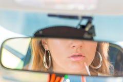 La muchacha del espejo retrovisor del coche aplica el lápiz labial Foto de archivo