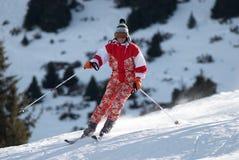 La muchacha del esquí gira la cuesta Imagenes de archivo