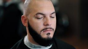 La muchacha del estilista afeita al hombre de la barba en barbería almacen de video