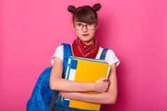 La muchacha del estudiante abraza la carpeta de papel colorida aislada en el fondo rosado, señora lista para el trabajo serio en  imágenes de archivo libres de regalías