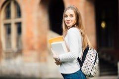 La muchacha del estudiante al aire libre con el bolso y los libros acercan a la universidad Fotografía de archivo libre de regalías