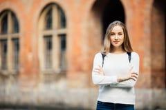 La muchacha del estudiante al aire libre con el bolso y los libros acercan a la universidad Fotos de archivo