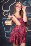La muchacha del estudiante con el paquete de libros presenta cerca de la pizarra Fotografía de archivo