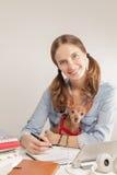 La muchacha del estudiante con un pequeño perro Fotos de archivo