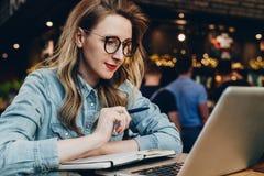 La muchacha del estudiante en vidrios de moda se sienta en café delante del ordenador, webinar educativo de los relojes del orden imagen de archivo libre de regalías