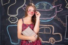La muchacha del estudiante en vidrios rojos con los libros acerca a la pizarra de la escuela Fotografía de archivo