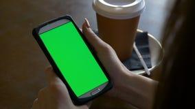 La muchacha del estudiante estudia usando el teléfono elegante en modo de retrato con café en una tabla almacen de video