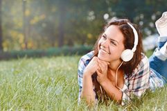 La muchacha del estudiante pone en hierba y música que escucha en parque Imagen de archivo