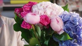 La muchacha del florista hace un ramo en un salón de la flor, primer metrajes