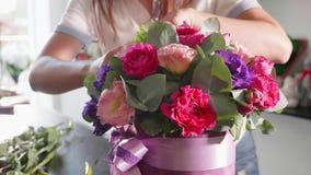 La muchacha del florista hace una caja floral en un salón de la flor, primer metrajes