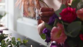 La muchacha del florista hace una caja floral en un salón de la flor, primer almacen de metraje de vídeo