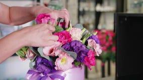 La muchacha del florista hace una caja floral en un salón de la flor, primer almacen de video