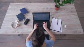 La muchacha del Freelancer dibuja un gr?fico en tablero y texto que mecanograf?a en el teclado del ordenador port?til que se sien almacen de video