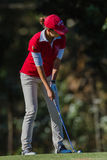 La muchacha del golf juega colores del hierro Imagen de archivo libre de regalías