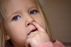 La muchacha del hábito escoge su nariz, finger en nariz foto de archivo
