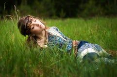 La muchacha del Hippie miente en la hierba Fotos de archivo libres de regalías