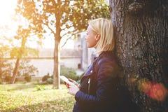 La muchacha del inconformista con buen humor es teléfono de célula de tenencia, mientras que está disfrutando de día caliente dur Fotografía de archivo
