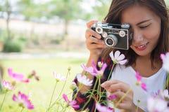 La muchacha del inconformista con el tiroteo del foco de la cámara del vintage florece en Garde Fotos de archivo libres de regalías