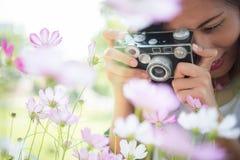 La muchacha del inconformista con el tiroteo del foco de la cámara del vintage florece en Garde Foto de archivo libre de regalías