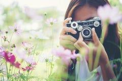 La muchacha del inconformista con el tiroteo del foco de la cámara del vintage florece en Garde Imagen de archivo libre de regalías