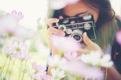 La muchacha del inconformista con el tiroteo del foco de la cámara del vintage florece en Garde Imagenes de archivo