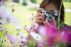 La muchacha del inconformista con el tiroteo del foco de la cámara del vintage florece en Garde Fotografía de archivo libre de regalías