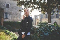 La muchacha del inconformista en buen humor está llamando por teléfono vía el teléfono de célula durante tiempo libre Fotografía de archivo