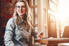 La muchacha del inconformista en vidrios de moda se sienta en café en la tabla delante de imágenes de archivo libres de regalías